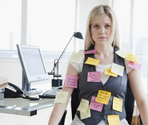 Business woman with sticky notes stuck to her at office